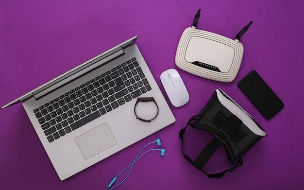 Gadget e dispositivi per giovani moderni su sfondo viola. vista dall'alto. lay piatto
