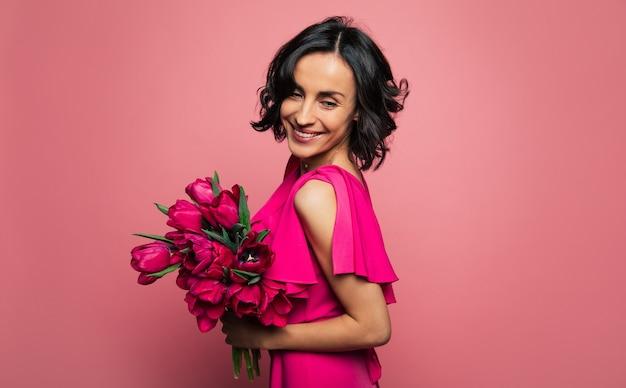 Bellezza modesta. ritratto di una ragazza felicissima, che si macchia di traverso e guarda in basso, mentre tiene in mano un bel mazzo di fiori.