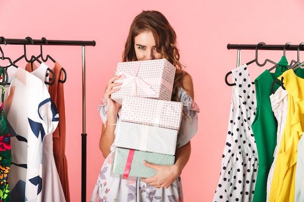 Modesta donna che indossa un abito in piedi in negozio vicino appendiabiti con scatole presenti isolato sul rosa