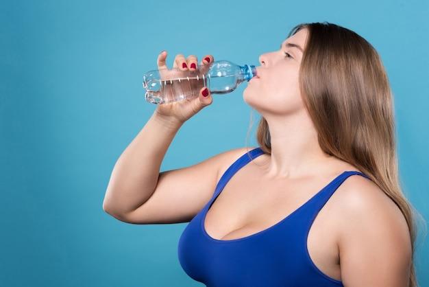 Inumidisci il tuo corpo. primo piano vista laterale della giovane donna in sovrappeso acqua potabile dalla bottiglia.