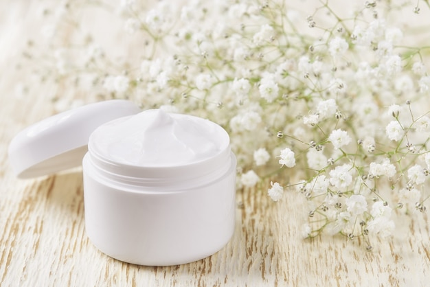Lozione idratante o crema per il corpo in un barattolo bianco su un tavolo di legno, copia spazio per il testo.