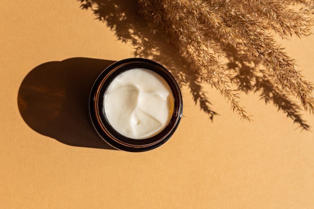 Vaso crema idratante in bottiglia di vetro ambrato e canne di fiori secchi su fondo beige. disposizione piana, vista dall'alto. set per prodotti di bellezza per la cura della pelle e del corpo