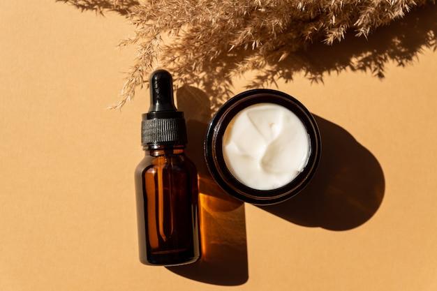 Vaso crema idratante, siero in bottiglia di vetro ambrato e canne di fiori secchi su fondo beige. disposizione piana, vista dall'alto. set per prodotti di bellezza per la cura della pelle e del corpo.
