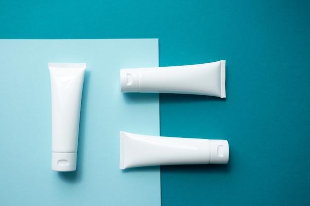 Mockup di tubi di plastica bianca crema idratante per le mani su sfondo blu carta alla moda, vista dall'alto.