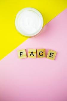 Crema cosmetica idratante in vasetto di vetro, su fondo giallo-rosa, lettere in legno sul tavolo.