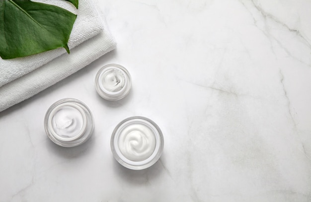 Barattoli contenitore crema idratante con asciugamano e foglia su sfondo marmo. vista piana, vista dall'alto.