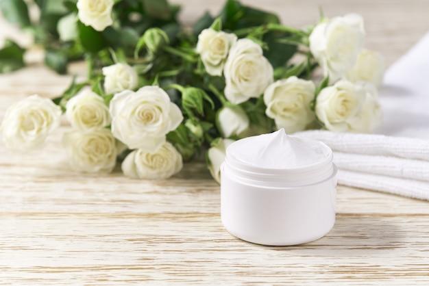 Crema idratante per prodotti per la cura della pelle della pelle sensibile in barattolo di plastica bianca con asciugamano sul tavolo di legno.