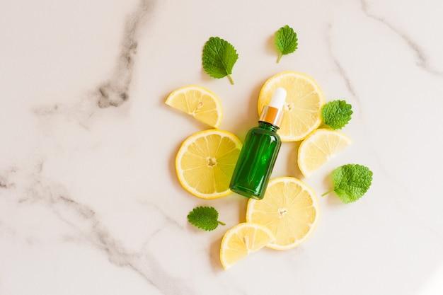 Olio di limone idratante in una bottiglia con una pipetta sullo sfondo di fette di limone succoso e foglie di menta fresca. vista dall'alto.