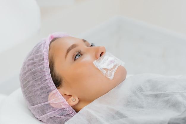 Idratare le labbra durante una procedura cosmetica per donna.