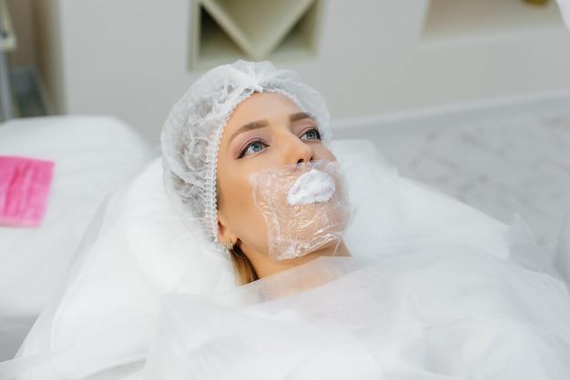 Idratare le labbra durante una procedura cosmetica per una ragazza. cosmetologia.