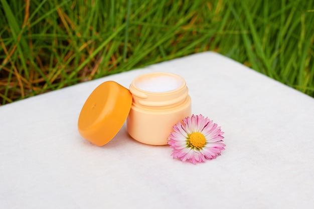 Crema corpo idratante e tonificante con fiori selvatici su uno sfondo di erba verde, cura della pelle del viso, bellezza, spa, cosmetici.