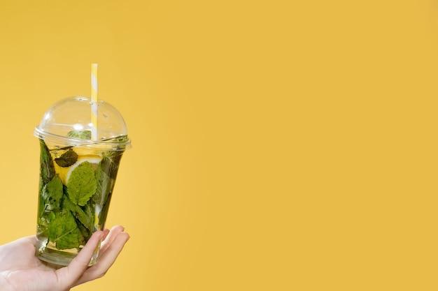 Cocktail mojito in un bicchiere di plastica con un tubo su uno sfondo giallo bevanda fresca in estate per t...
