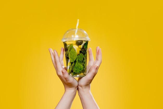 Cocktail mojito in un bicchiere di plastica con un tubo su sfondo giallo. bevanda fresca in estate da asporto. posto per il testo.