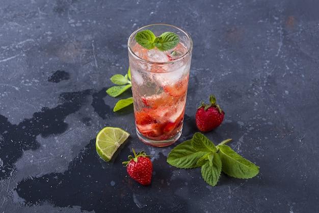 Cocktail mojito con cubetti di ghiaccio su sfondo grigio strutturato