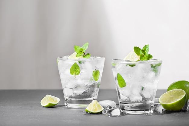 Cocktail mojito con lime e menta in vetro su uno sfondo di pietra grigia