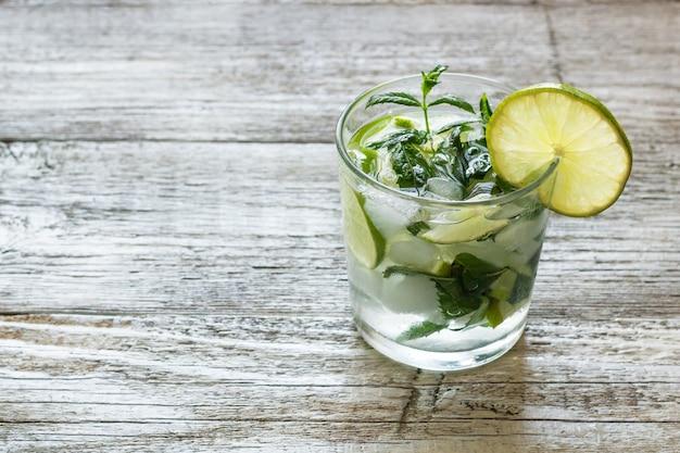 Cocktail mojito con calce e menta in un bicchiere highball su uno sfondo di legno bianco copia spazio.