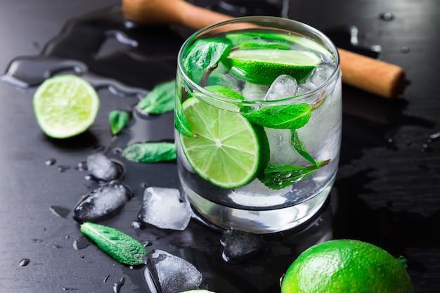 Cocktail mojito con calce, foglie di menta e cubetti di ghiaccio su sfondo nero.