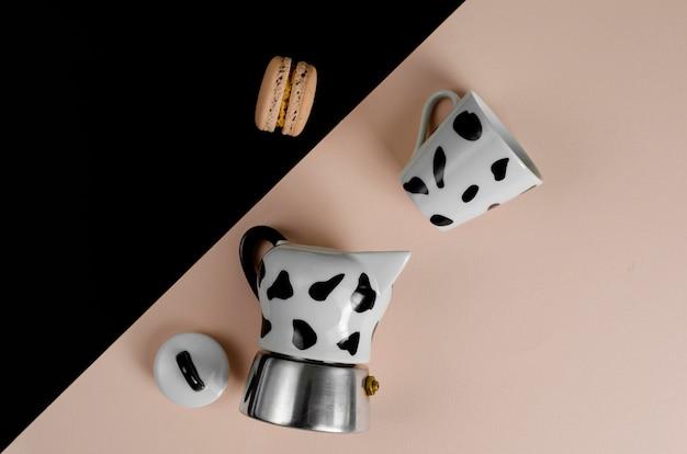 Caffettiera moka caffettiera italiana con una tazza e amaretto su beige e nero