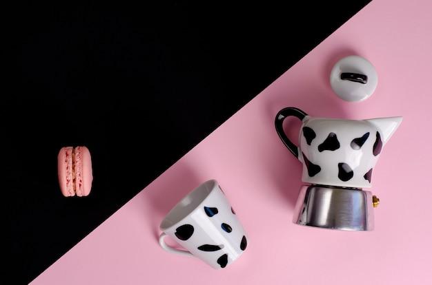 Caffettiera moka caffettiera italiana con una tazza e amaretto su rosa pastello e nero