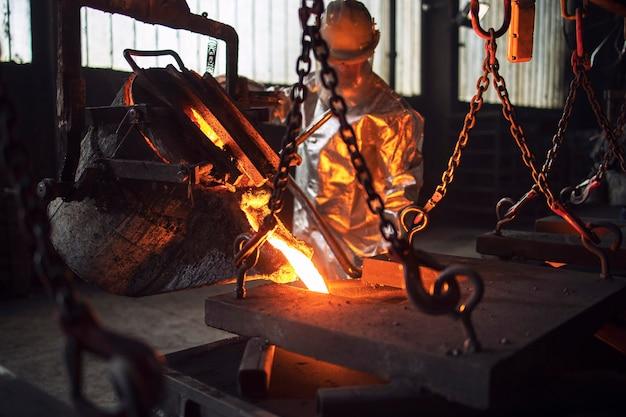 Metallo fuso che viene colato in stampi in fonderia.