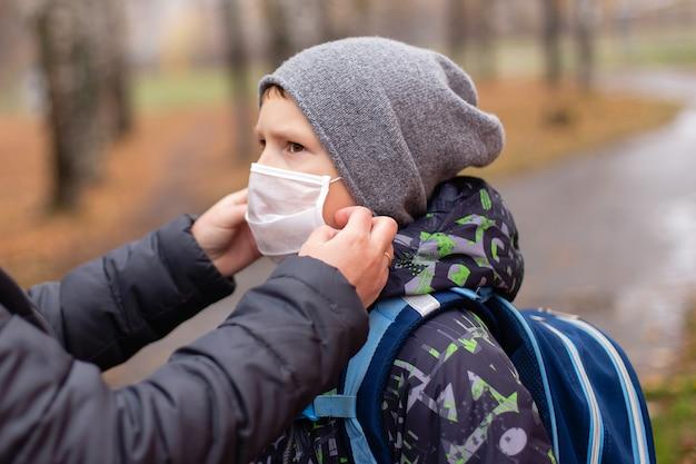 La mamma aggiusta la maschera al bambino per strada