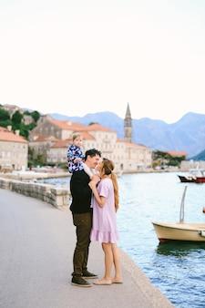 La mamma bacia quasi il papà sorridente con la figlia sulle spalle sulla costa sullo sfondo di