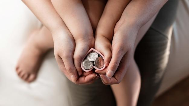 La mamma e il bambino si tengono per mano il cuore con i soldi. il concetto di alfabetizzazione economica e finanziaria. contributo di successo al futuro. primo piano di una mano con monete.