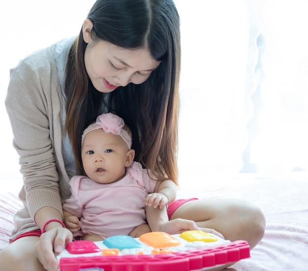 Mamma e bambino che giocano giocattolo sul letto.