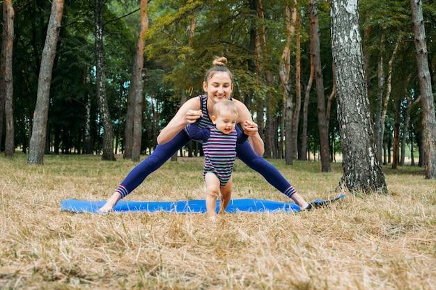 Mamma e bambino yoga benessere all'aperto lezione di yoga per famiglie che praticano consapevolezza e meditazione fisica