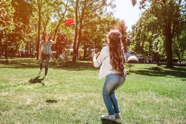 Mamma e bambino sono in piedi davanti a un altro e giocano con il frisbee