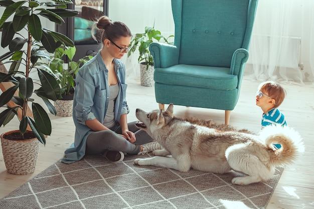 Mamma e bambino si divertono e giocano con il cane a casa Foto Premium