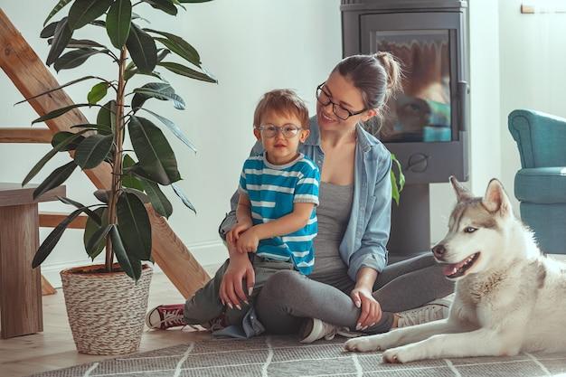 Mamma e bambino si divertono e giocano con il cane a casa