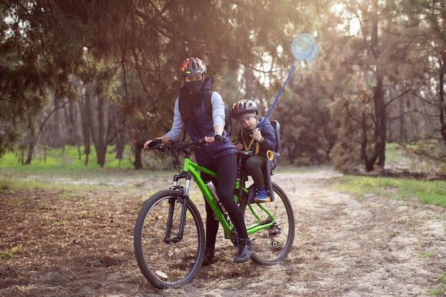 Mamma e bambino con i caschi vanno in bicicletta nella foresta
