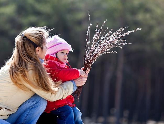 Mamma e bambino che tengono i fiori di salice nelle loro mani e li guardano. foto all'aperto, sfondo sfocato