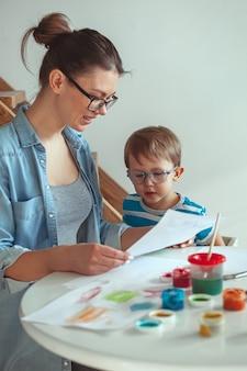 Mamma e bambino dipingono insieme a casa con il cane