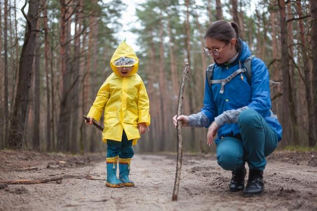 Mamma e bambino camminano insieme nella strada forestale dopo la pioggia in impermeabili