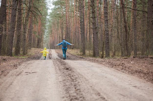 Mamma e bambino che camminano insieme lungo la strada forestale dopo la pioggia in impermeabili, vista posteriore