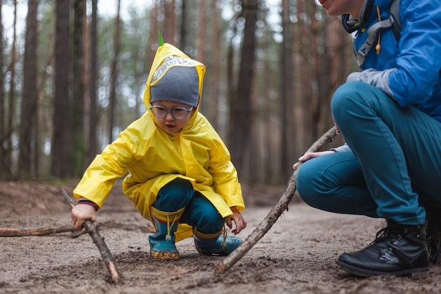 Mamma e bambino che camminano lungo la strada forestale dopo la pioggia in impermeabili, disegnano insieme sulla sabbia con bastoncini di legno