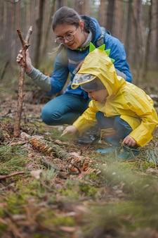 Mamma e bambino che camminano insieme nella foresta dopo la pioggia in impermeabili, guardando i funghi su un albero caduto e parlando