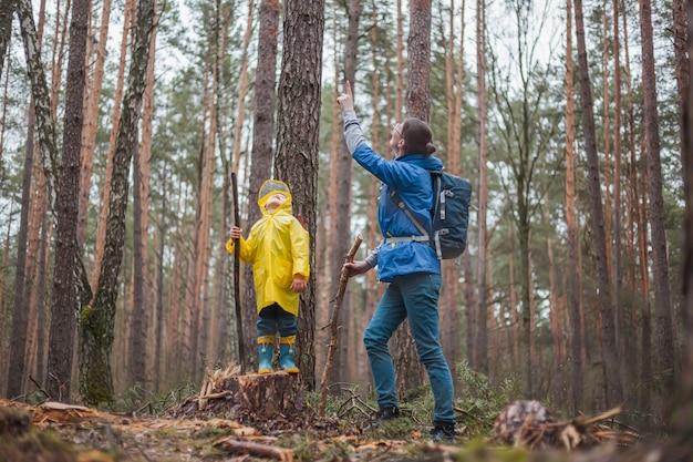 Mamma e bambino che camminano insieme nella foresta dopo la pioggia in impermeabili, guardando il cielo