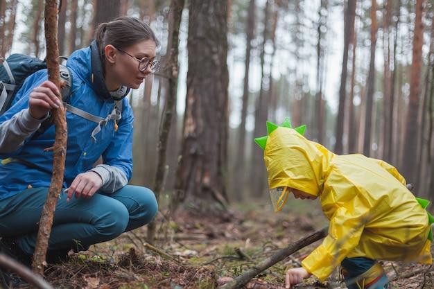 Mamma e bambino che camminano insieme nella foresta dopo la pioggia in impermeabili