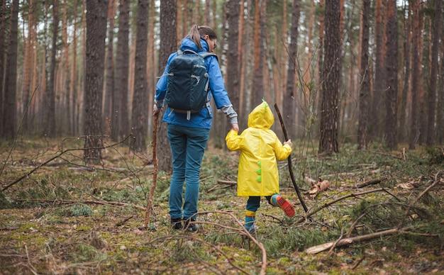 Mamma e bambino che camminano nella foresta dopo la pioggia in impermeabili con bastoni di legno in mano, vista posteriore