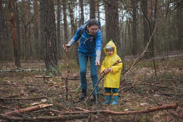 Mamma e bambino che camminano nella foresta dopo la pioggia in impermeabili con bastoni di legno nelle mani