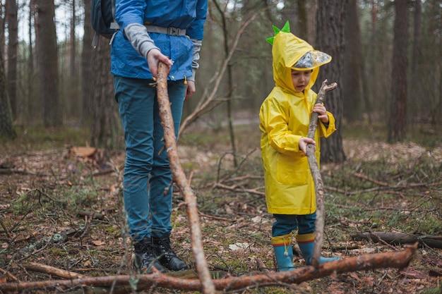 Mamma e bambino che camminano nella foresta dopo la pioggia in impermeabili con bastoni di legno in mano