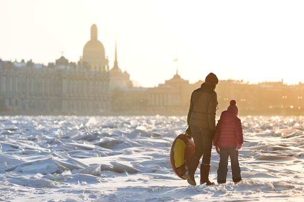 Mamma e bambino che camminano sul ghiaccio del fiume ghiacciato nella soleggiata giornata invernale, paesaggio urbano sullo sfondo