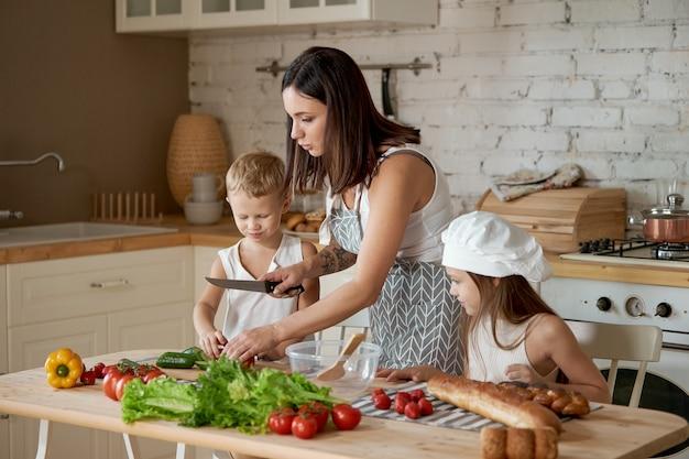 La mamma prepara il pranzo con i bambini. una donna insegna a sua figlia a cucinare da suo figlio. vegetarismo e cibo sano e naturale