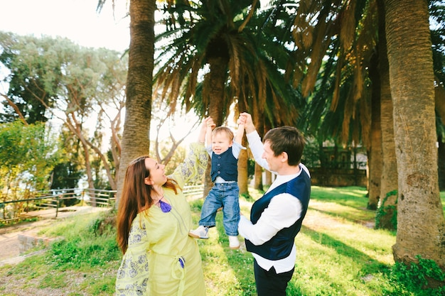 Mamma e papà tengono il loro bambino per mano sotto le palme in una giornata di sole