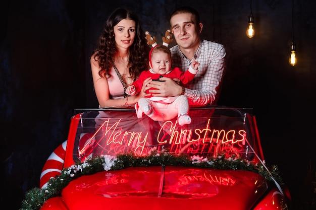 Mamma, papà e neonata che si divertono nella retro automobile rossa di natale. genitori con una piccola figlia in una sessione fotografica di natale.