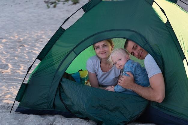 Mamma papà e bambino in tenda turistica al campeggio. vacanze di famiglia.