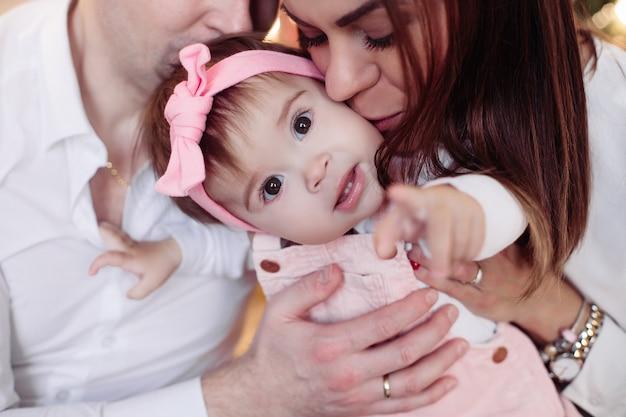 Mamma, papà e figlia sono bellissimi e felici che si abbracciano nell'atmosfera del nuovo anno
